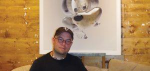 François Boutet présente des icônes populaires qui l'intéressent, il pose ici avec sa toile de Mickey. Photo : Amélie Légaré